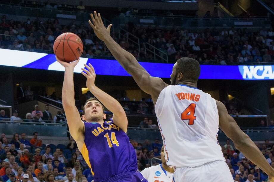 UAlbany Great Danes forward Sam Rowley (14) puts up a shot with Florida Gators center Patric Young (4) defending during the first half of the NCAA second round game, Thurday afternoon, March 20, 2014, in Orlando, FLA. (Gregory Fisher/Special to the Times Union) Photo: GF / SportsThroughTheLens.com