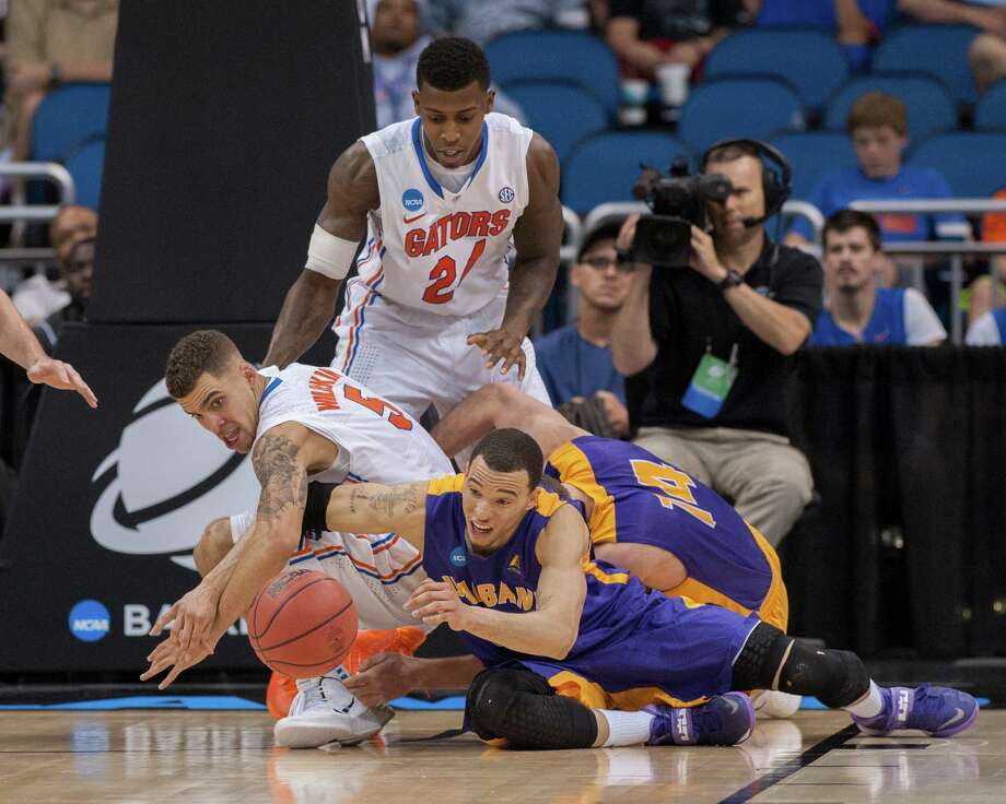 Florida Gators guard Scottie Wilbekin (5) left, and UAlbany Great Danes forward Gary Johnson (20) right, scramble for the loose ball during the second half of the NCAA second round game, Thurday afternoon, March 20, 2014, in Orlando, FLA. (Gregory Fisher/Special to the Times Union) Photo: GF / SportsThroughTheLens.com