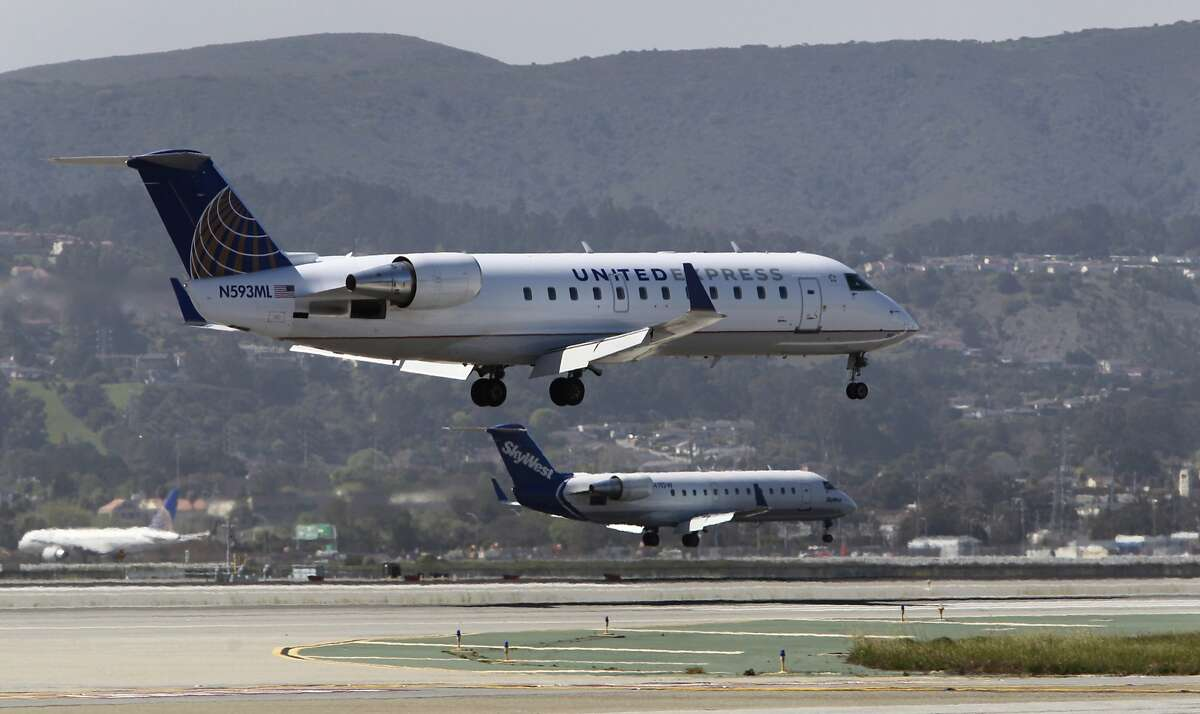 FILE - Regional commuter jets land on parallel runways 28L and 28R at San Francisco International Airport in San Francisco, Calif. on Thursday, March 20, 2014. SFO will be shutting down Runway 28L for 20 days in September to reconstruct the base layer.