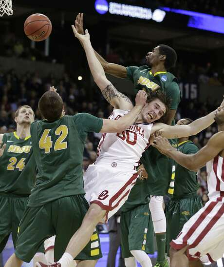 Oklahoma's Ryan Spangler is squeezed out by North Dakota State's Marshall Bjorklund (42) and TrayVonn Wright. Photo: Elaine Thompson / Associated Press / AP