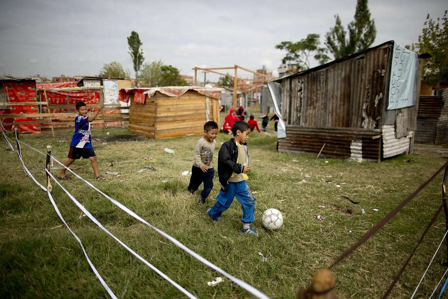 Children play soccer near makeshift shelters in a squatters' settlement of more than 500 residents who have named it the Pope Francis neighborhood, in a Buenos Aires suburb, Argentina, Thursday, March 20, 2014. The squatters who occupied the land in demand for housing solutions some weeks ago, now fear they will be evicted after a judge ratified the eviction order Wednesday. (AP Photo/Natacha Pisarenko) Photo: Natacha Pisarenko, Associated Press