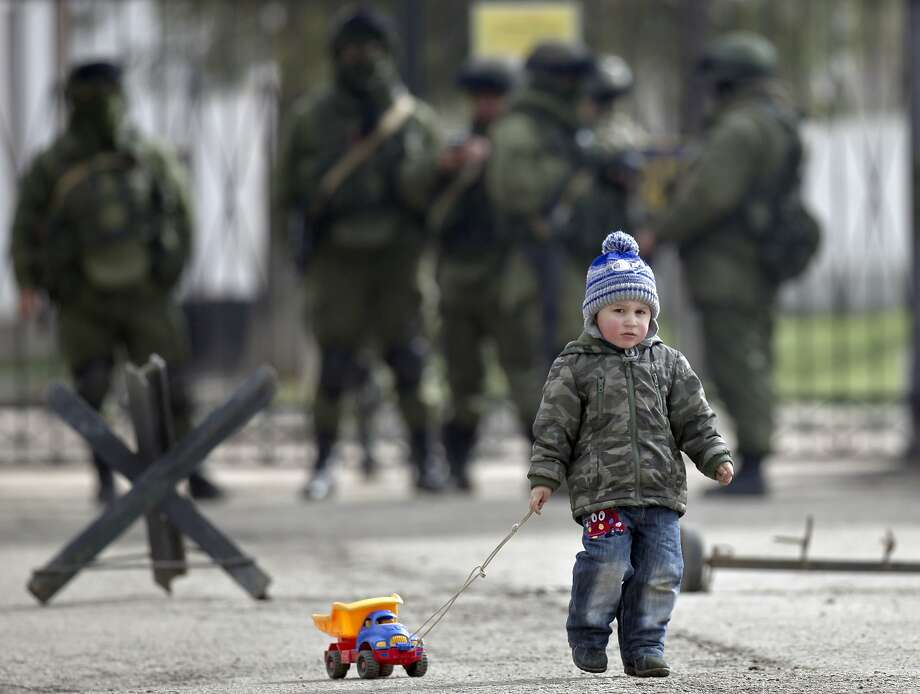 A child drags a toy truck past pro-Russian soldiers standing outside an Ukrainian military base in Perevalne, Crimea, Thursday, March 20, 2014. With thousands of Ukrainian soldiers and sailors trapped on military bases, surrounded by heavily armed Russian forces and pro-Russia militia, the Kiev government said it was drawing up plans to evacuate its outnumbered troops from Crimea back to the mainland and would seek U.N. support to turn the peninsula into a demilitarized zone.(AP Photo/Vadim Ghirda) Photo: Vadim Ghirda, Associated Press