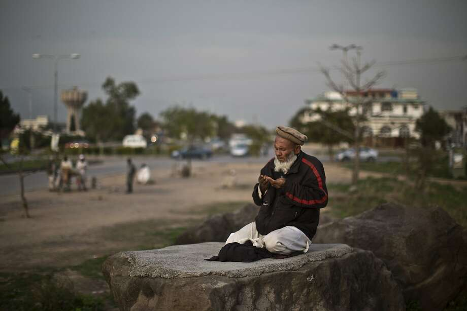 An elderly Pakistani man offers prayers while he and other men wait on a roadside to be hired as a daily laborers in Islamabad, Pakistan, Thursday, March 20, 2014. AP Photo/Muhammed Muheisen) Photo: Muhammed Muheisen, Associated Press