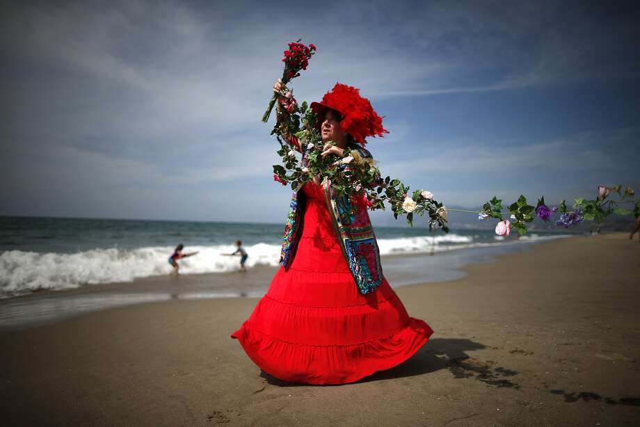 Spring de Haviland hands out carnations on the beach to celebrate the first day of spring in Santa Monica, California March 20, 2014. Spring officially began on Thursday in the northern hemisphere, and is known as both the spring or vernal equinox. REUTERS/Lucy Nicholson (UNITED STATES - Tags: SOCIETY TRAVEL ENVIRONMENT) Photo: Lucy Nicholson, Reuters