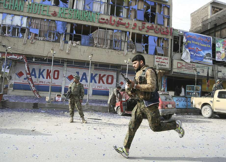 Afghan police officers arrive to the scene after a multi-pronged attack on a police station in Jalalabad, the capital of eastern Nangarhar province, Afghanistan, Thursday, March 20, 2014. Taliban insurgents staged the attack, using a suicide bomber and gunmen to lay siege to the station, government officials said. Two remotely detonated bombs also exploded nearby. (AP Photo/Rahmat Gul) Photo: Rahmat Gul, Associated Press