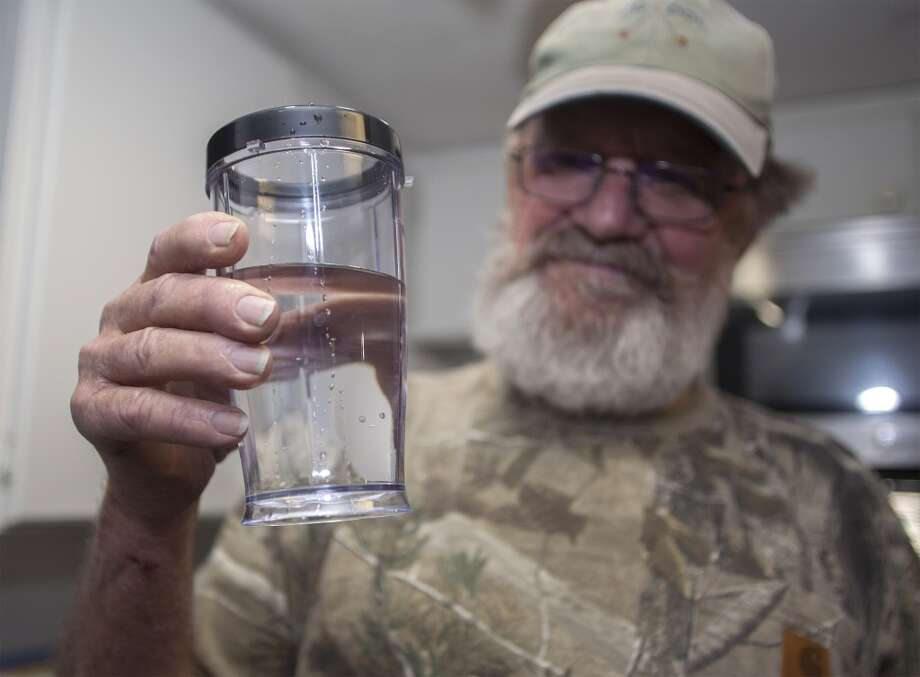 "Flemington Road community member Sam Malpass of Wilmington, N.C. holds a glass of water from his home on Wednesday, Feb. 19, 2014. Malpass and his wife Pat are part of a small community near L.V. Sutton Complex operated by Duke Energy they feel could be polluting well water with spill off and seepage from large coal ash ponds. ""If you want to know what it's like living near a coal ash pond, this is it,"" said Malpass, 67, a retired carpenter and Vietnam veteran. ""We're afraid to drink the water because we don't know what's in it. We can't eat the fish because we don't know if it's safe anymore. It's changed our lives out here."" Photo: Randall Hill, AP"
