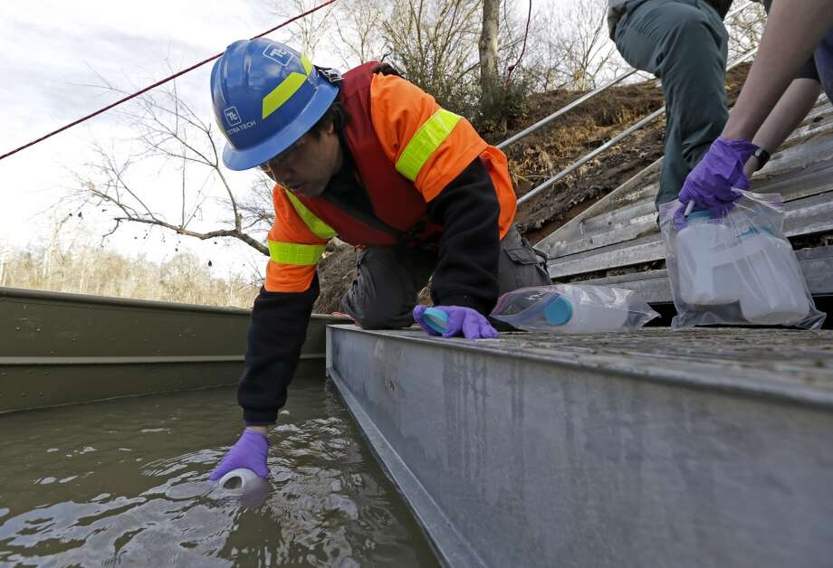 Didi Fung, a contractor for the Environmental Protection Agency, collects water samples from the Dan River on Feb. 5, 2014. State and federal environmental officials continued their investigations of a spill of coal ash into the Dan River in Eden, N.C. Documents and interviews collected by The Associated Press show how Duke''s lobbyists prodded Republican legislators to tuck a 330-word provision in a regulatory reform bill running nearly 60 single-spaced pages. Though the bill never once mentions coal ash, the change allowed Duke to avoid any costly cleanup of contaminated groundwater leaching from its unlined dumps toward rivers, lakes and the drinking wells of nearby homeowners. Photo: Gerry Broome, AP