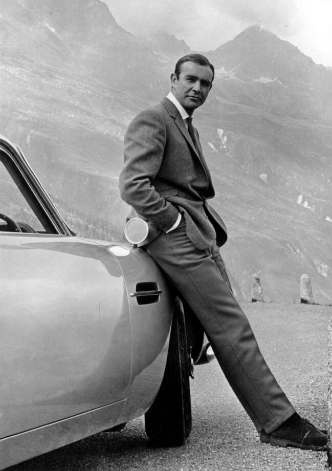 "Actor Sean Connery poses as James Bond next to his Aston Martin DB5 in a scene from ""Goldfinger"" in 1964 . Photo: Michael Ochs Archives, Getty Images"