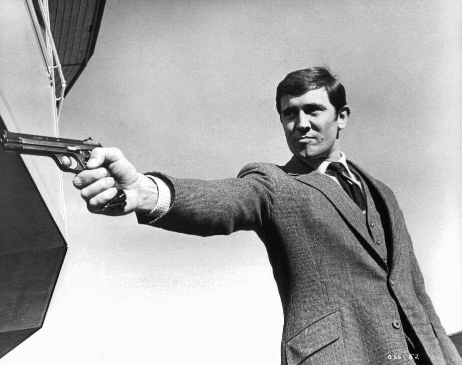 George Lazenby takes aim as he has a showdown with Spectre Chief Blofeld in a scene from the film 'On Her Majesty's Secret Service', 1969.  A three piece suit accessorized with a firearm is a Bond signature. Photo: Archive Photos, Getty Images