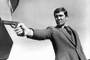 George Lazenby takes aim as he has a showdown with Spectre Chief Blofeld in a scene from the film 'On Her Majesty's Secret Service', 1969.  A three piece suit accessorized with a firearm is a Bond signature.