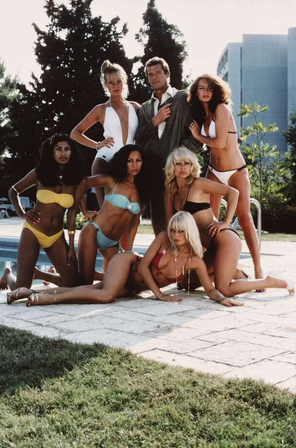English actor Roger Moore as 007, surrounded by bikini-clad women in a publicity still for the James Bond film 'For Your Eyes Only', February 1981. Out of all the Bonds Moore was the most playful: his slightly more of-the-era seventies takes on the Bond tux and suit standout in the franchise. Photo: Keith Hamshere, Getty Images