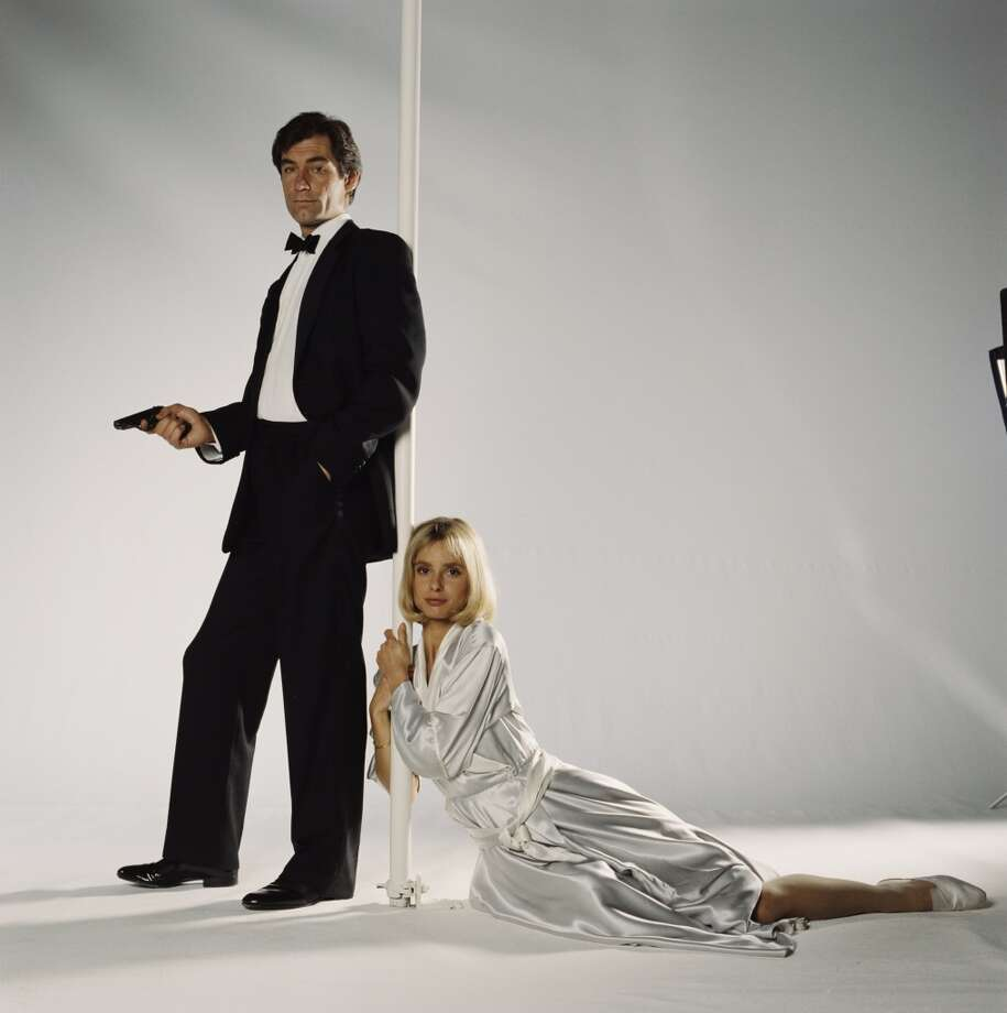 Timothy Dalton as 007 and actress Maryam d'Abo as Kara Milovy in a publicity still for the 1987 James Bond film 'The Living Daylights', 1986. He is holding his trademark Walther PPK. Note the loose, wide 1980's pant on the tuxedo. Photo: Keith Hamshere, Getty Images