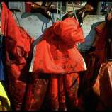 Oil soiled cleanup workers' garments hanging on pegs in aftermath of Exxon Valdez oil spill.