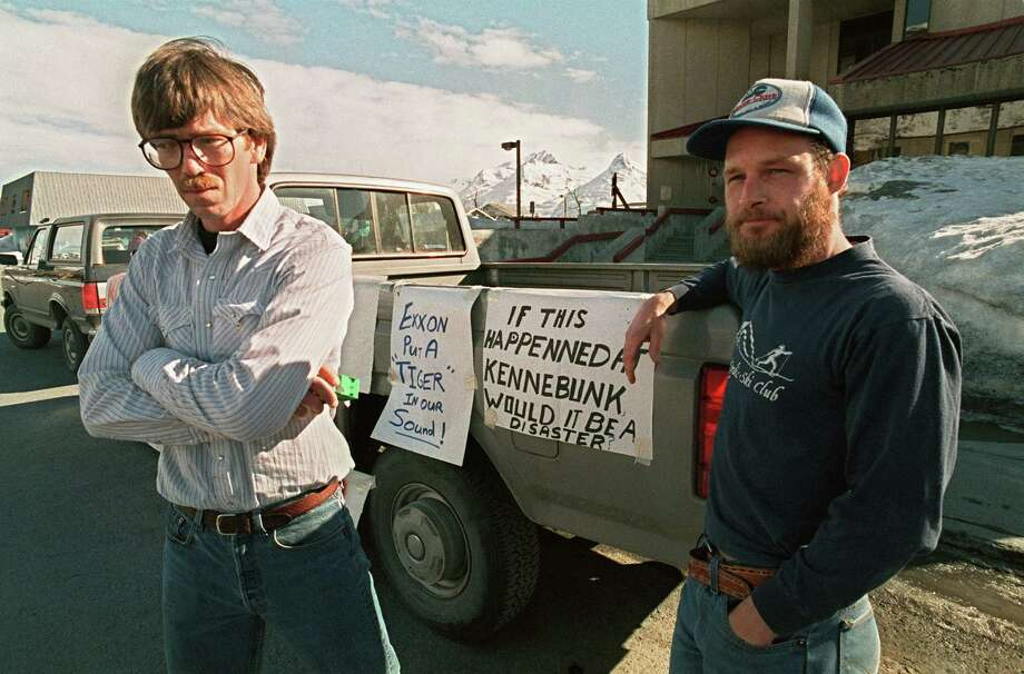 Fishermen Greg Will (L) and Matt Kinney, both of Valdez, stand in protest outside an Exxon news conference room which was closed to local residents in Valdez, more a week after the beginning of an oil disaster which occurred when the tanker Exxon Valdez ran aground and spilled 11 million gallons of crude oil into Prince William Sound off Alaska. Photo: CHRIS WILKINS, AFP/Getty Images / 2013 AFP