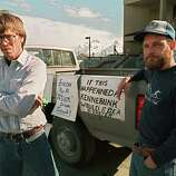 Fishermen Greg Will (L) and Matt Kinney, both of Valdez, stand in protest outside an Exxon news conference room which was closed to local residents in Valdez, more a week after the beginning of an oil disaster which occurred when the tanker Exxon Valdez ran aground and spilled 11 million gallons of crude oil into Prince William Sound off Alaska.