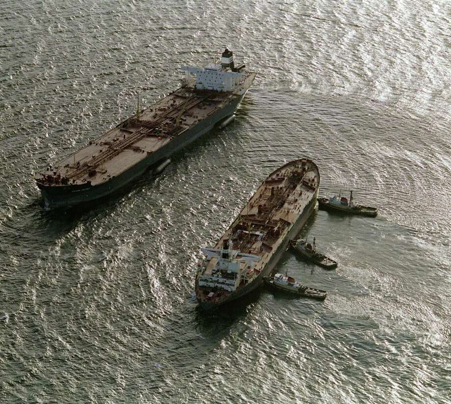 Three tugboats (R)  push the oil tanker Exxon San Francisco (C) into place beside the crippled tanker Exxon Valdez (L) in Prince William Sound to begin off-loading the remainder of crude oil in Valdez, a week after the beginning of an oil disaster which occurred when the tanker Exxon Valdez ran aground and spilled 11 million gallons of crude oil into Prince William Sound off Alaska. Photo: CHRIS WILKINS, AFP/Getty Images / 2013 AFP