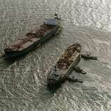 Three tugboats (R)  push the oil tanker Exxon San Francisco (C) into place beside the crippled tanker Exxon Valdez (L) in Prince William Sound to begin off-loading the remainder of crude oil in Valdez, a week after the beginning of an oil disaster which occurred when the tanker Exxon Valdez ran aground and spilled 11 million gallons of crude oil into Prince William Sound off Alaska.