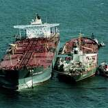 Tugboats hold the tanker Exxon Baton Rouge, right, up against the tanker Exxon Valdez as oil is pumped out of the damaged tanker that ran aground into the Prince William Sound, 25 miles from Valdez, Alaska, March 28, 1989.  Exxon Valdez ran aground March 24, spilling over 270,000 barrels of crude oil.