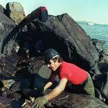 Rick Zufelt of Soldotna, Alaska, wipes spilled crude oil off a rock on the beach of Naked Island on Prince William Sound, Alaska, Friday morning, April 7, 1989, in an effort to clean the remnants of the Exxon Valdez tanker disaster of March 24.  Zufelt, who works for a company contracted by Exxon to clean up the oil, is using a special oil absorbent rag.