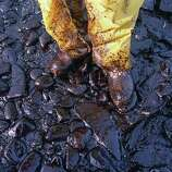 Thick crude oil washed up on the cobble beach of Evans Island sticks to the boots and pants of a local fisherman in Prince William Sound, Alaska, on April 11, 1989.  The Exxon Valdez tanker oil spill on March 24 has blackened hundreds of miles of coastline.