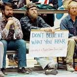 Three unidentified men listen to Exxon Oil officials, in Cordova, Alaska on March 29, 1989, talk about the millions of gallons of oil that spilled from one of their tankers after it ran aground in Prince William Sound.