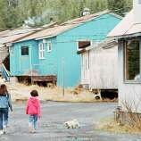 Two unidentified children walk through the village of Tatitlek, May 17, 1989, Tatitlek, Alaska. Life in this fishing village is uncertain since the Exxon Valdez hemorrhaged more than 10 million gallons of crude oil just 5 miles from their cove. Though local folks have seen little of the oil in their waters, the oil spill has jeopardized the fishing season, on which the village depends.