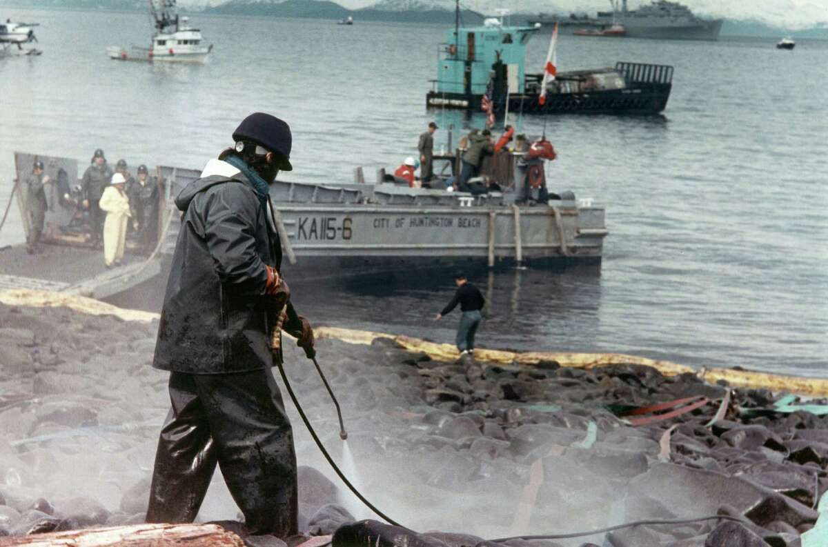 An oil spill worker sprays high pressure water on the rocks at Smith Island, Alaska, fouled by the Exxon Valdez oil spill, but the technique is recognized by workers to be basically worthless.