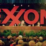 Exxon Corp president Lee Raymond, left, addresses the company's shareholders during their annual meeting, Thursday, May 18, 1989, Parsippany, New Jersey. Company chairman Lawrence Rawl is at right. About 250 demonstrators gathered outside the suburban hotel where the meeting was held, about 35 miles west of New York City. Man in center is unidentified.