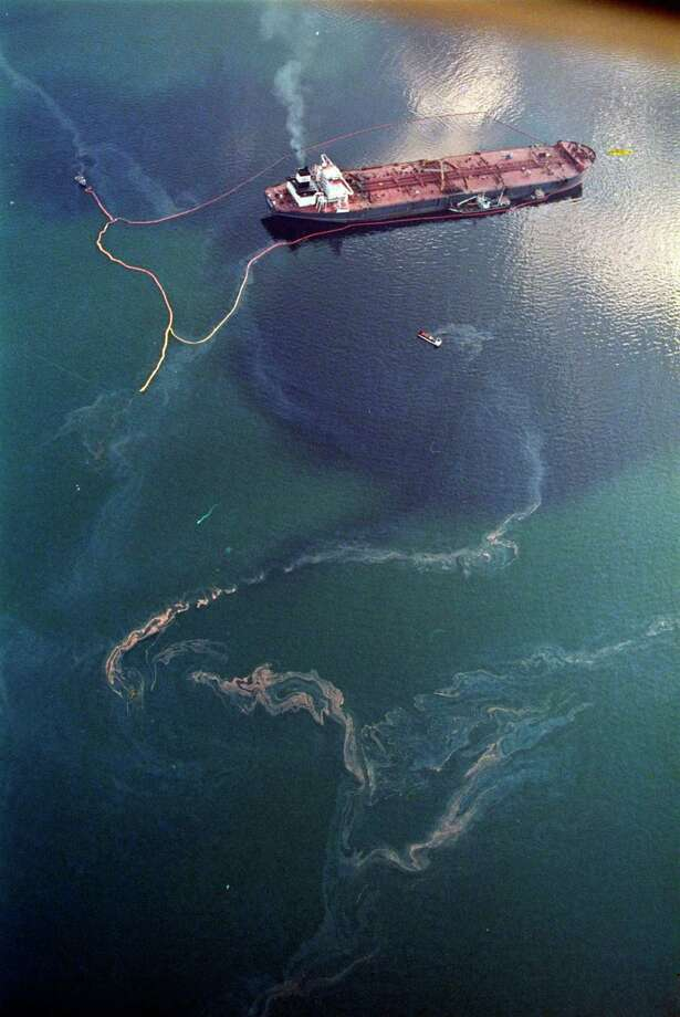 Crude oil from the tanker Exxon Valdez, top, swirls on the surface of Alaska's Prince William Sound near Naked Island. The 987-foot tanker, carrying 53 million gallons of crude, struck Bligh Reef at 12:04 a.m. on March 24, 1989, and within hours unleashed an estimated 10.8 million gallons of thick, toxic crude oil into the water. Storms and currents then smeared it over 1,300 miles of shoreline. Twenty five years later, the region, its people and its wildfire are still recovering. Photo: John Gaps III, ASSOCIATED PRESS / AP2014