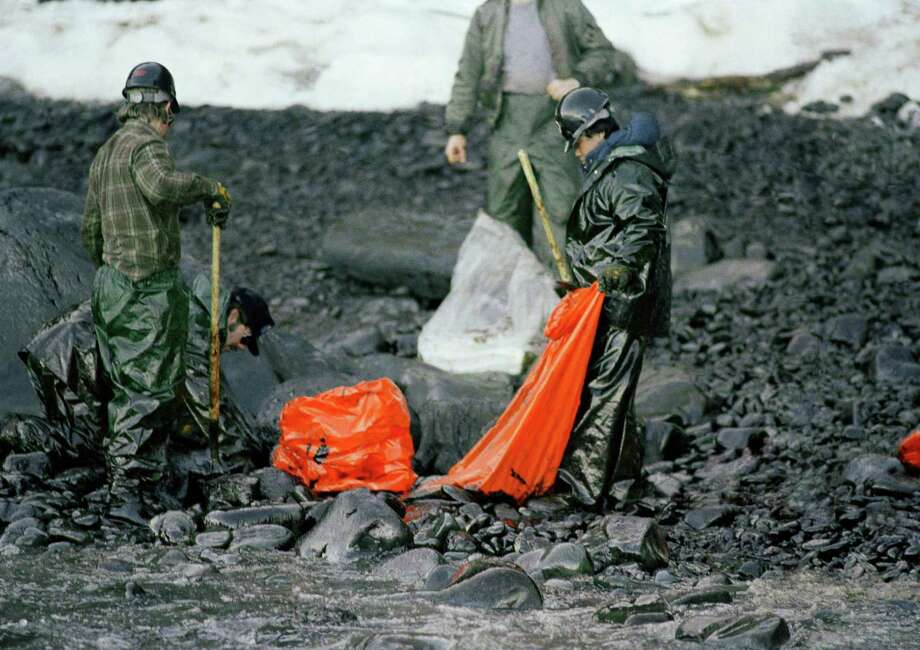 Workers try to remove globs of oil from Baked Island in Prince William Sound, Alaska. A massive oil slick covers Prince William Sound stretching over 100 miles as the result of the tanker Exxon Valdez running aground March 24, 1989, spilling more than 10-million gallons of oil.  25 years after the Exxon Valdez oil spill off the coast of Alaska, some damage heals, some effects linger in Prince William Sound. Photo: Jack Smith, ASSOCIATED PRESS / A1989