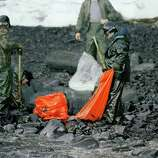 Workers try to remove globs of oil from Baked Island in Prince William Sound, Alaska. A massive oil slick covers Prince William Sound stretching over 100 miles as the result of the tanker Exxon Valdez running aground March 24, 1989, spilling more than 10-million gallons of oil.  25 years after the Exxon Valdez oil spill off the coast of Alaska, some damage heals, some effects linger in Prince William Sound.