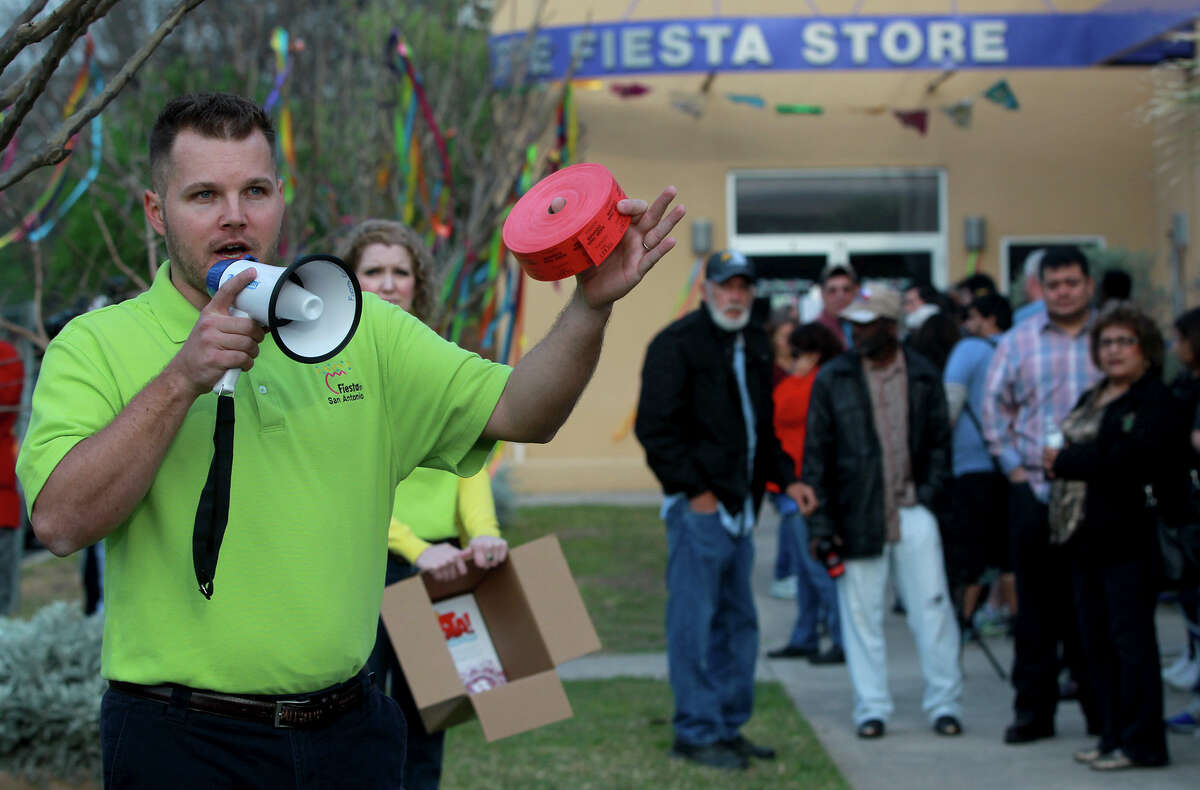 Nick Kaylor (left), Director of Operations for the Fiesta Commission, explains to people Friday March 21, 2014 how tickets to Fiesta events can obtained at the Fiesta Store on Broadway. Tickets to 19 Fiesta events are available through a process of random numbers being drawn and some event tickets are also available at area retail outlets.Tickets to events can also be obtained online.