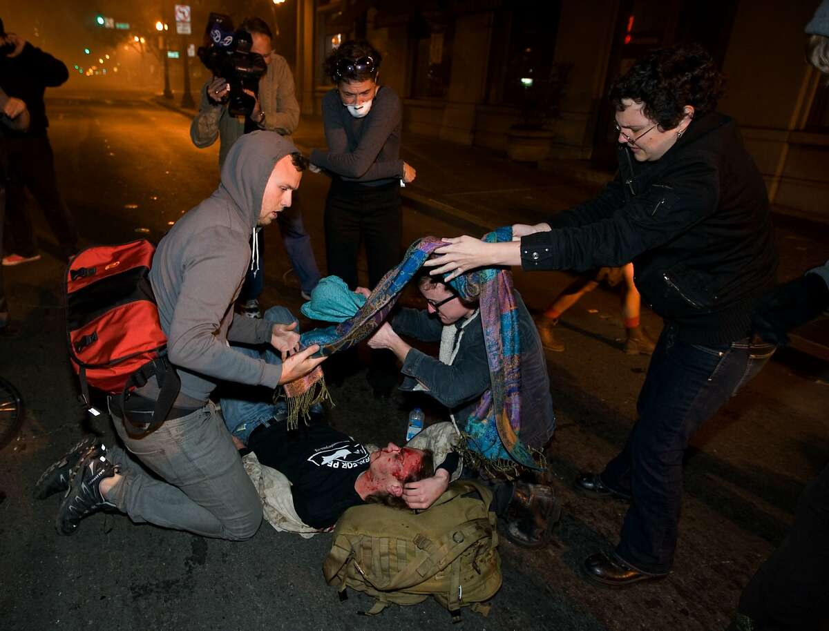 Occupy Wall Street protesters help 24-year-old Iraq War veteran Scott Olsen as he lies on the ground bleeding from a head wound Tuesday, Oct. 25, 2011, in Oakland, Calif. Olsen was critically injured by an object that struck him in the head during the chaotic conflict.
