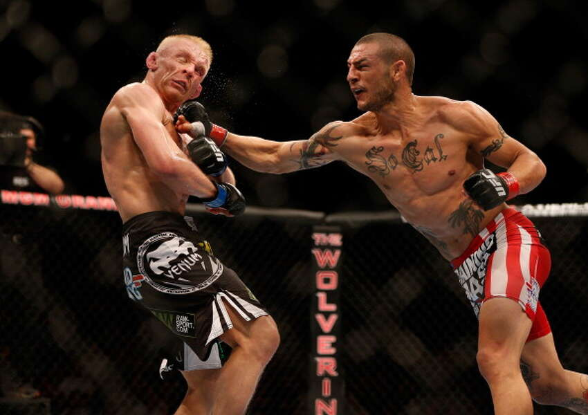 LAS VEGAS, NV - JULY 06: (R-L) Cub Swanson punches Dennis Siver in their featherweight fight during the UFC 162 event inside the MGM Grand Garden Arena on July 6, 2013 in Las Vegas, Nevada.