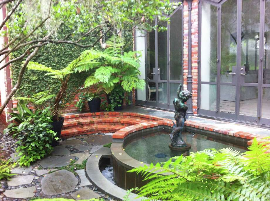 A large garden includes sculpture and diverse plantings.