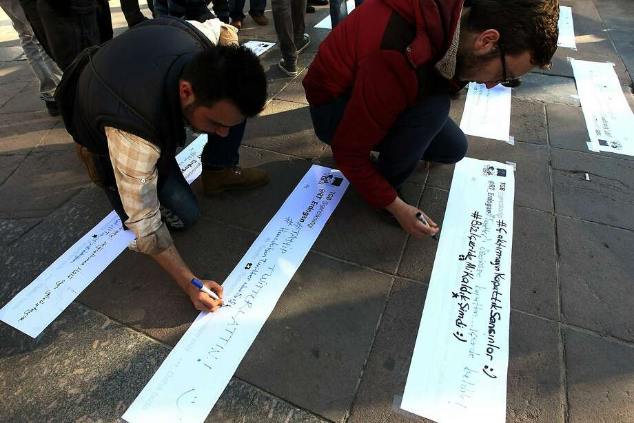 People write slogans during a protest after the government blocked access to Twitter in Ankara. Photo: Adem Altan, AFP/Getty Images