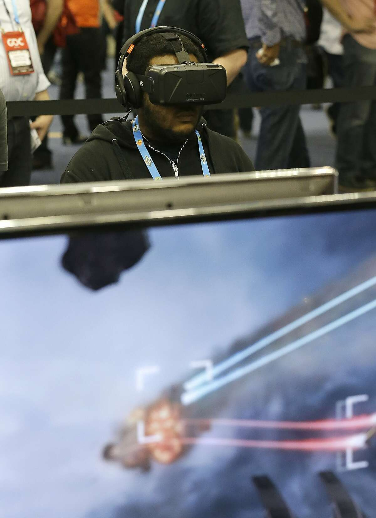 Gabriel Burgess tests out the Oculus virtual reality headset at the Game Developers Conference 2014 in San Francisco, Wednesday, March 19, 2014. (AP Photo/Jeff Chiu)