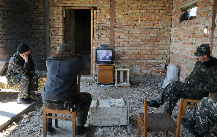 TOPSHOTS Ukrainian pilots watch TV displaying Russian President Vladimir Putin's speach as they sit in an unfinished building at the Belbek air -base not far from the Crimean city of Sevastopol on March 21, 2014. Surly and dejected, many Ukrainian soldiers at Perevalne base in Crimea deserted their posts Friday, crossing groups of buoyant Russian soldiers moving in -- but 200 were said to be resisting. Overwhelmed by superior force and on the day Russia formally claimed the Black Sea peninsula as its territory, the biggest base still holding out against a creeping month-long invasion was slowly giving up.  AFP PHOTO/ VIKTOR DRACHEVVIKTOR DRACHEV/AFP/Getty Images Photo: Viktor Drachev, AFP/Getty Images