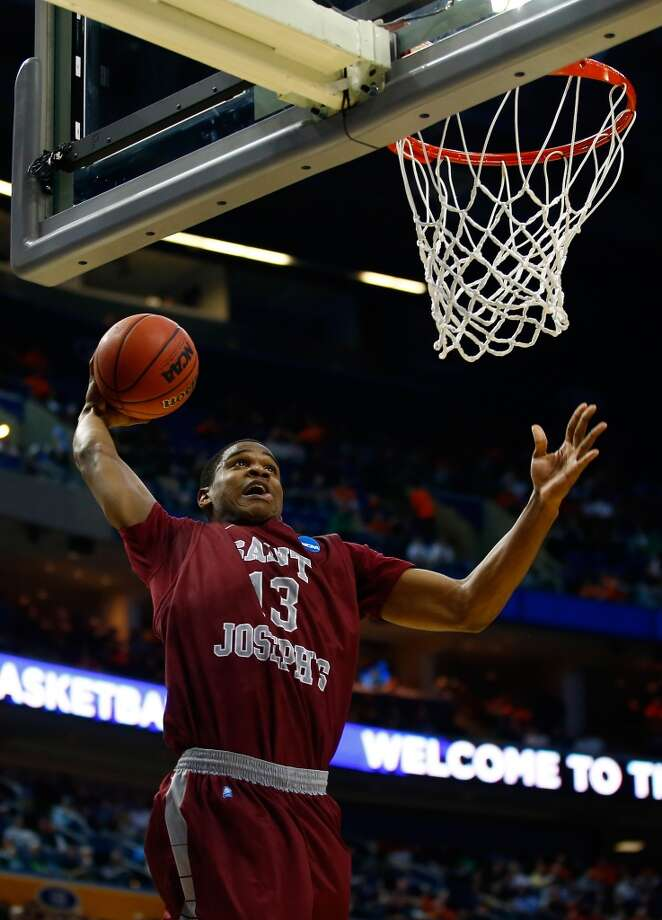 Ronald Roberts Jr. of St. Joseph propels for a dunk against Connecticut. Photo: Jared Wickerham, Getty Images