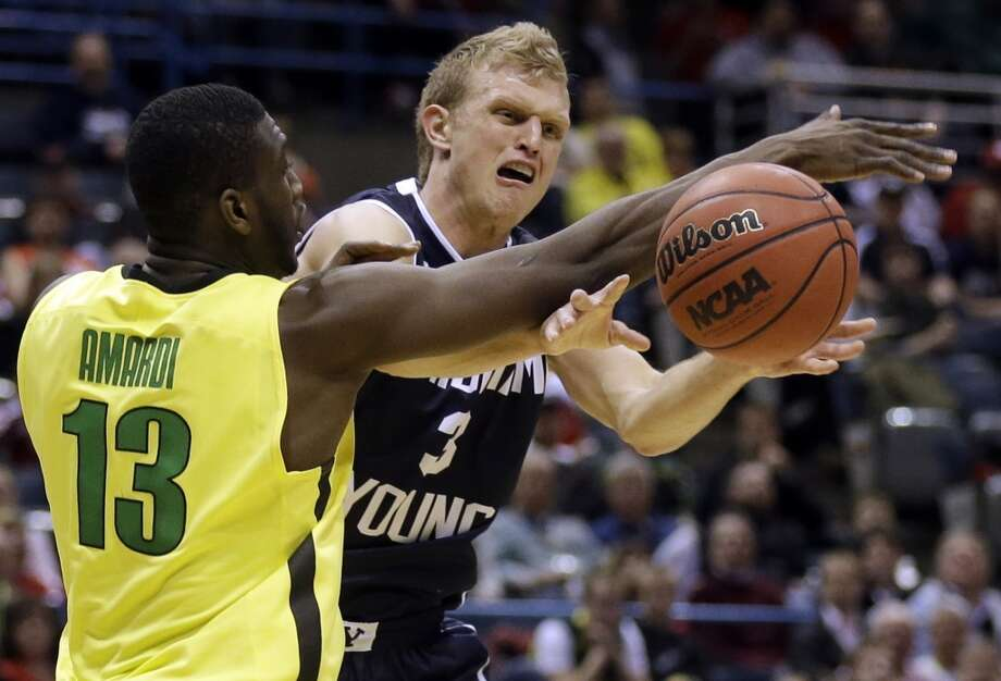 BYU guard Tyler Haws passes the ball against Oregon forward Richard Amardi during the second half. Photo: Jeffrey Phelps, Associated Press