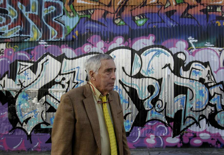 Property owner Laurance Mathews views the work of taggers and graffiti artists defacing buildings on Erie Alley at Van Ness. Photo: Paul Chinn, The Chronicle