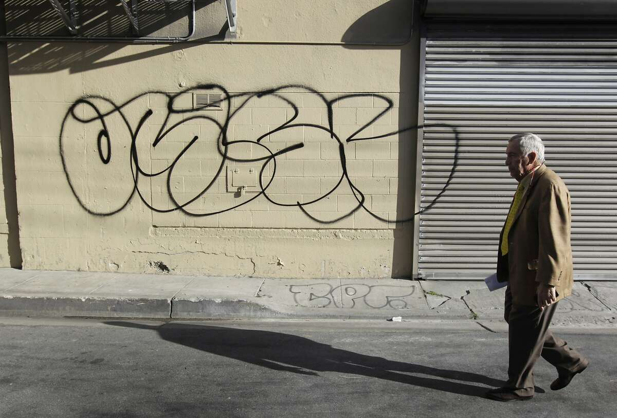 Property owner Larry Matthews walks past graffiti defacing his building on Erie Alley and South Van Ness Avenue in San Francisco, Calif. on Thursday, March 20, 2014. Matthews says he spends $15,000 annually to cover graffiti on the building and is not happy with the city's current graffiti eradication policy.