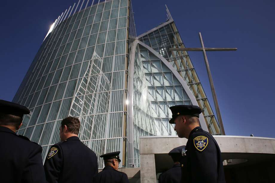 Police Officer Jorge Garcia (right) stands outside the Cathedral of Christ the Light in Oakland after a memorial Mass marked the fifth anniversary of the fatal shooting of four Oakland police officers. Photo: Mike Kepka, The Chronicle