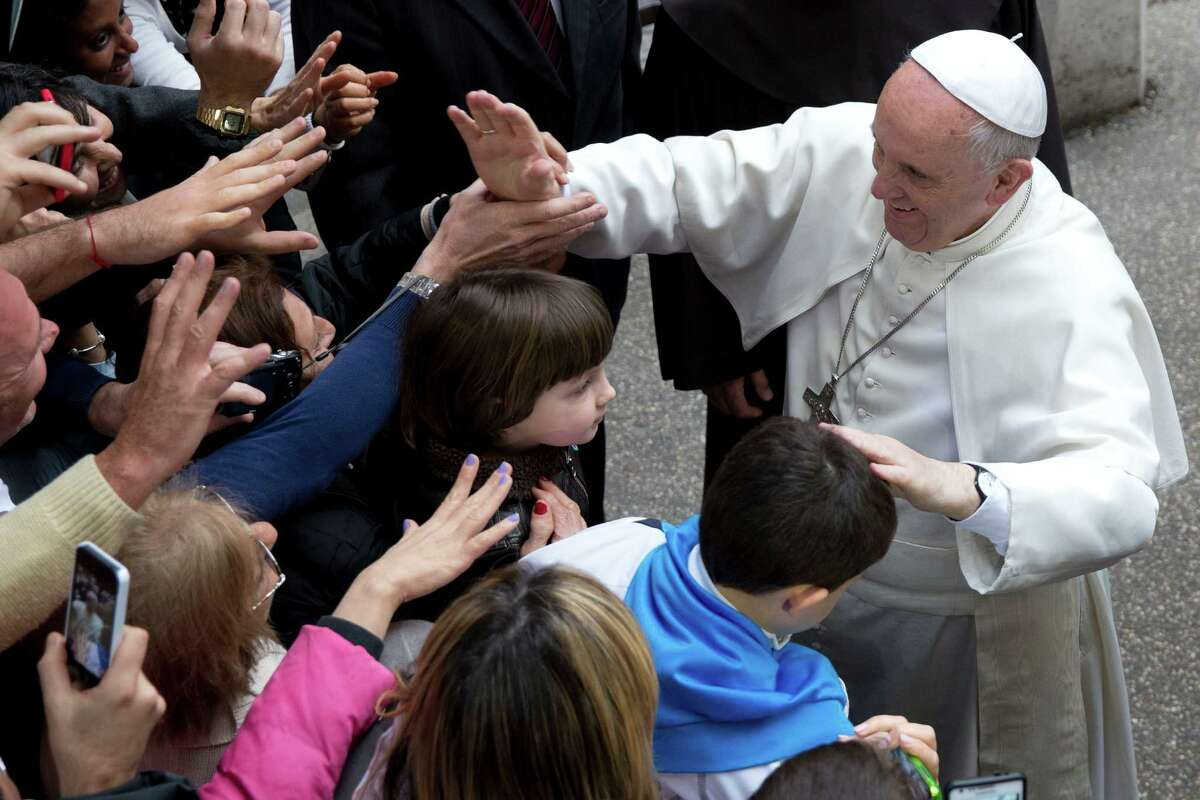 Pope Francis greets faithful as he arrives for a meeting with relatives of innocent mafia victims, in Rome's St. Gregorio VII church, just outside the Vatican, Friday, March 21, 2014.