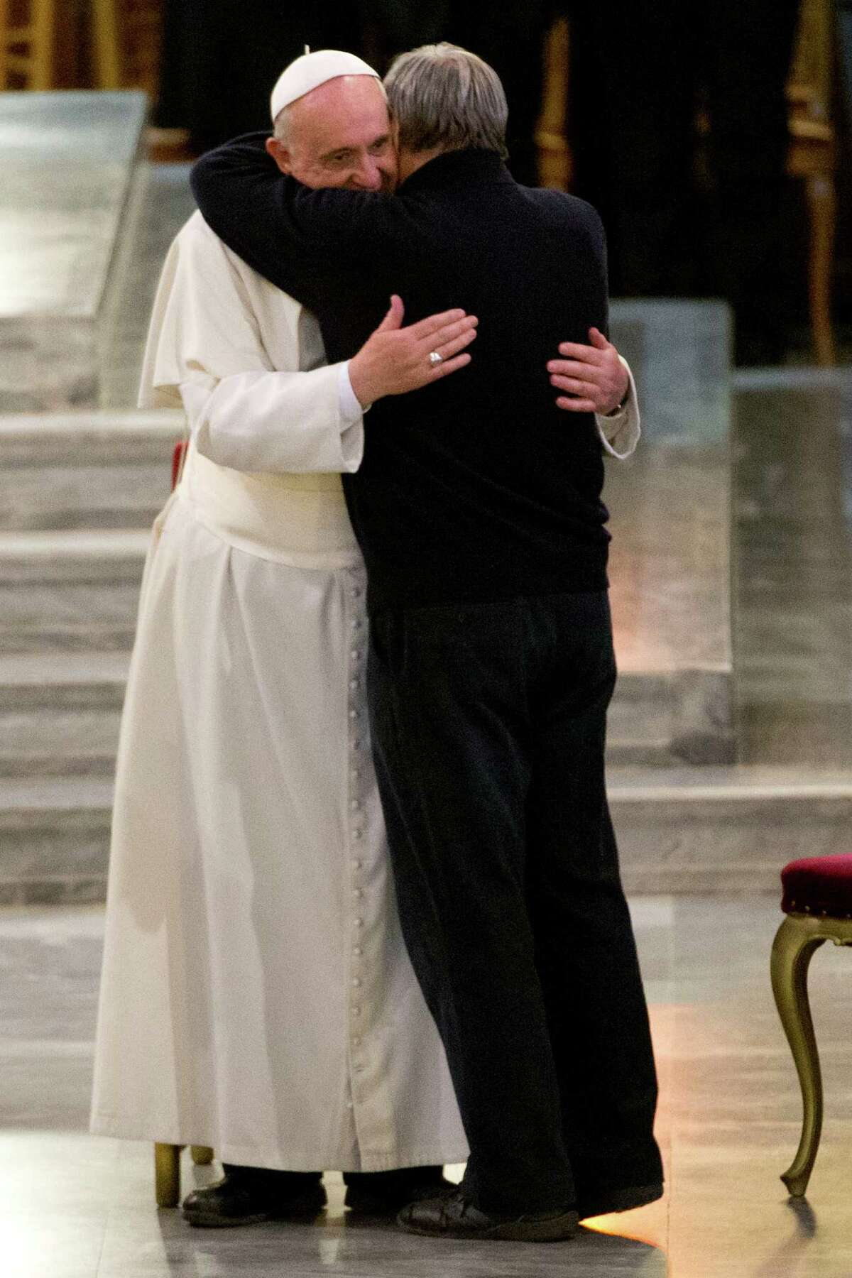 Pope Francis embraces Don Luigi Ciotti as he arrives for a meeting with relatives of innocent mafia victims, in Rome's St. Gregorio VII church, just outside the Vatican, Friday, March 21, 2014.