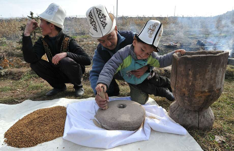 """And in the winter they used it for curling:A Kyrgyz man shows a boy how to grind grain with   an ancient millstone during Nowruz  celebrations on the outskirts of Kyrgyzstan's   capital Bishkek. Nowruz, """"New Year's"""" in Farsi, marks the first   day of spring in Central Asia. The flamboyant lids  are traditional Kyrgyz hats. Photo: Vyacheslav Oseledko, AFP/Getty Images"""