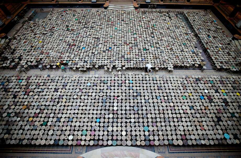 """What has 18,000 legs but doesn't move?A staff member helps set up Chinese artist Ai Weiwei's installation """"Stools"""" consisting of   6,000 stools in the atrium of the Martin-Gropius-Bau exhibition hall in Berlin. Photo: Kay Nietfeld, AFP/Getty Images"""