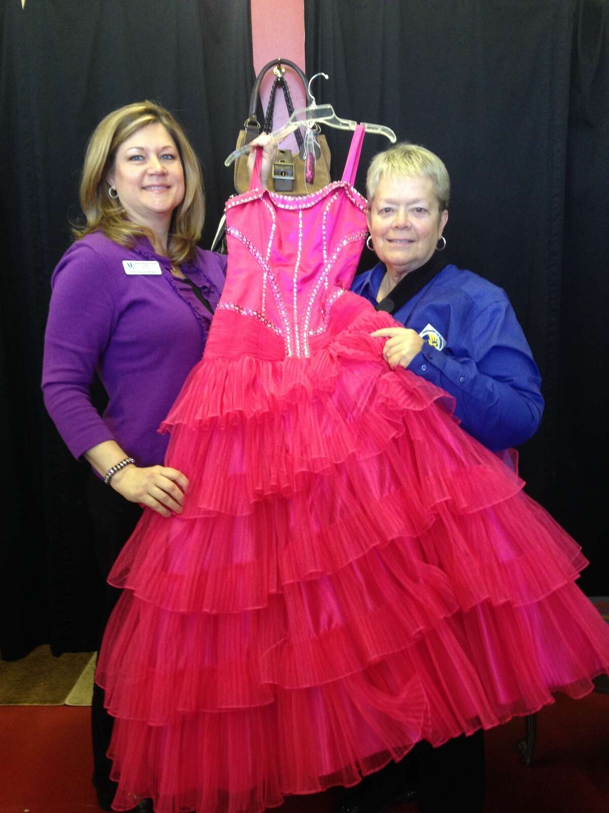 Chairman Ann Hammond and Vice Chairman Christina Deane display one of the many prom dresses that will be made available to high school senior women referred to the program through their respective schools.