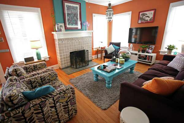 Fiona Arecchi chose a turquoise and terra cotta color palette for the living room. Justin Arecchi tiled the fireplace surround, and their son-in-law, Lee Williams, upholstered the sofa and chairs.