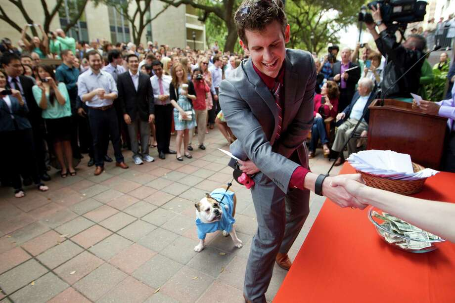 Adam Wright, walks with his dog, Moxie, to pick up his Match Day letter during a ceremony for the medical students at the University of Texas Health Science Center Medical School Friday, March 21, 2014, in Houston. Match Day is the culmination of a complex precess that matches graduating medical students with residency programs through the National Resident Matching Program. UT Health matched 231 students, with 49 percent staying in Texas. Photo: Brett Coomer, Houston Chronicle / © 2014 Houston Chronicle
